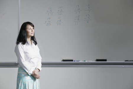 pedagogic: Portrait of a female teacher standing in a class room at school