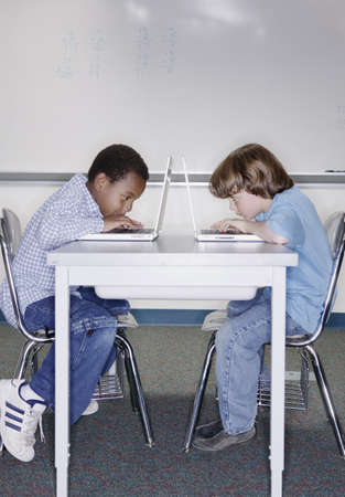pedagogic: Children working on laptops at shared desk