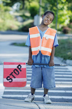 Portrait of a young boy crossing guard standing on the road holding a stop sign LANG_EVOIMAGES