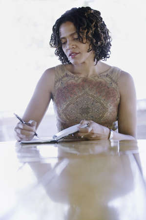 way of behaving: Woman sitting at a table writing in a book LANG_EVOIMAGES