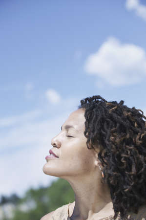 singly: Side profile of a woman sitting outdoors with eyes closed LANG_EVOIMAGES