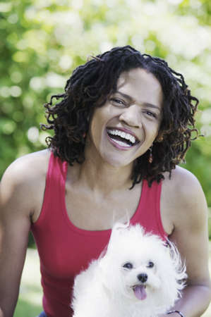 chirpy: Portrait of a woman in a park smiling holding a dog (Maltese)
