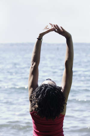 blase: Rear view of a woman with arms raised at the beach