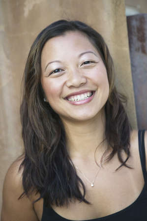 ebullient: Portrait of young woman looking at camera smiling