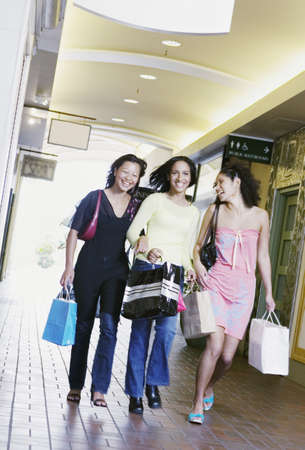 only 3 people: Three young women smiling walking together holding shopping bags