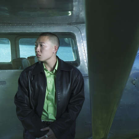 Young man resting on the side of a plane Stock Photo - 16043483