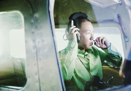 freewill: Male pilot in Cessna 110 adjusting his headset LANG_EVOIMAGES