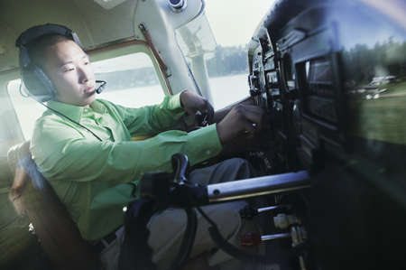 Male pilot in Cessna 110 adjusting his headset operating the controls Stock Photo - 16043489