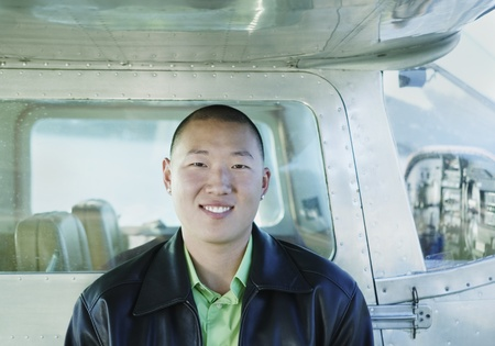 freewill: Portrait of a young man smiling leaning against the side of a plane