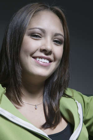 ebullient: Portrait of a young woman looking at camera smiling LANG_EVOIMAGES