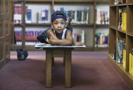 pedagogic: Young boy reading on bench in library