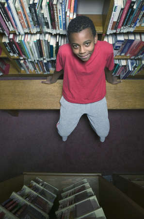 pedagogic: Portrait of a young boy sitting on a bench in a library looking up