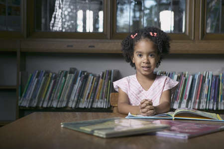 pedagogic: Portrait of a girl sitting at a table in a library