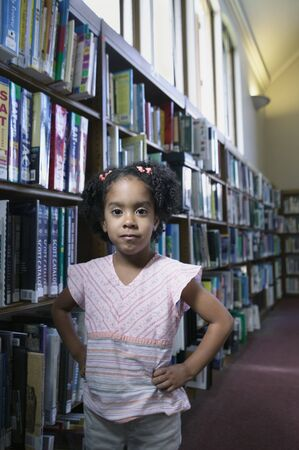 pedagogic: Portrait of a young girl standing with hands on her hips in a library