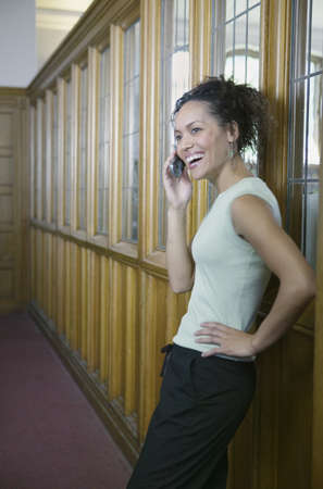 blase: Young woman leaning against a wall talking on a mobile phone