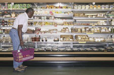 Elderly man shopping at a supermarket holding a shopping basket Stock Photo - 16043510