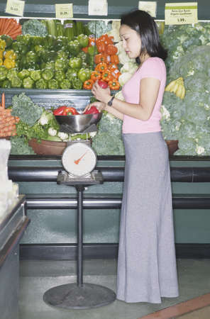 Side profile of a young woman weighing produce in grocery store Stock Photo - 16043511