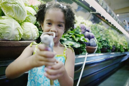 Portrait of a young girl standing holding a sprayer in the produce section of a supermarket Stock Photo - 16043512
