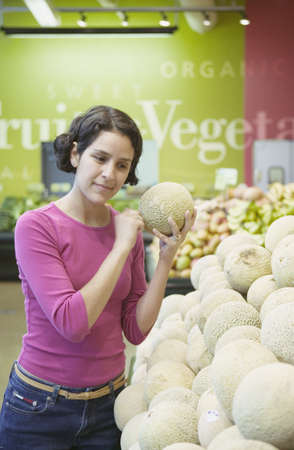 volition: Woman at a supermarket produce section checking a melon for ripeness LANG_EVOIMAGES