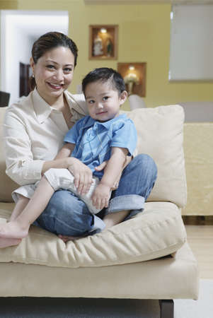 Portrait of a mother sitting on a couch with her son at home Stock Photo - 16043523