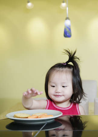 close up food: Young girl seated at a dining table reaching for food in a plate LANG_EVOIMAGES