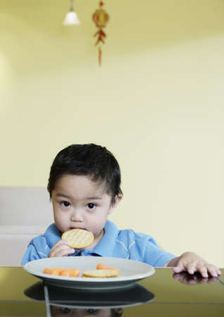 Portrait of a young boy seated at a table eating cookies LANG_EVOIMAGES
