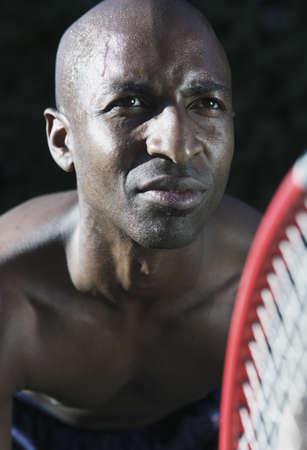 determines: Man bending forward holding a tennis racket