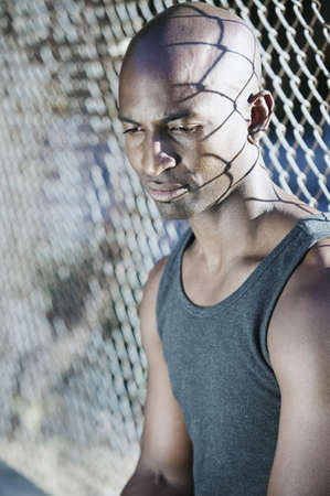 Man sitting next to a chain-link fence Stock Photo - 16043540