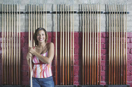 cue sticks: Portrait of a woman standing holding a cue stick in front of a wall with racks of cue sticks