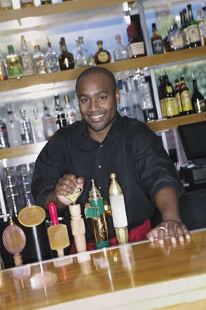 Young man smiling standing behind a bar Stock Photo - 16043549