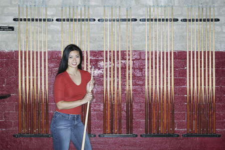 cue stick: Young woman standing holding a cue stick in front of a wall of racks of cue sticks