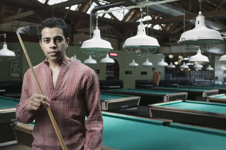 cue stick: Man holding pool a cue stick standing in a pool hall LANG_EVOIMAGES