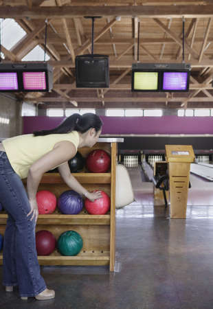 recourse: Woman selecting a bowling ball in bowling alley LANG_EVOIMAGES