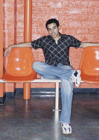 Young man sitting on orange chairs Stock Photo - 16043556