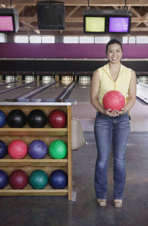 Young woman holding a bowling ball in a bowling alley Stock Photo - 16043459