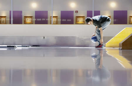 Side profile of a young man bowling in a bowling alley Stock Photo - 16043563