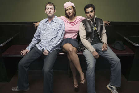 way of behaving: Young woman sitting with two young men LANG_EVOIMAGES
