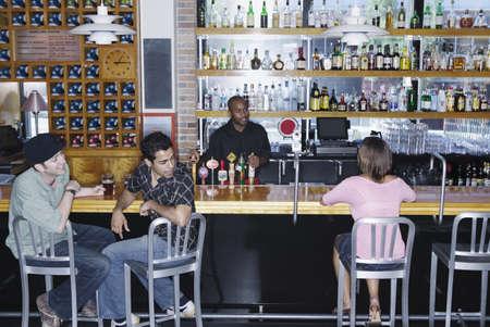 knees bent: Due giovani uomini seduti in un bar a guardare una giovane donna LANG_EVOIMAGES