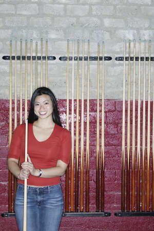cue stick: Young woman standing holding a cue stick LANG_EVOIMAGES