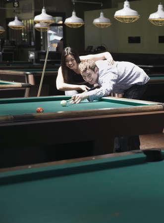 snooker hall: Young couple playing pool