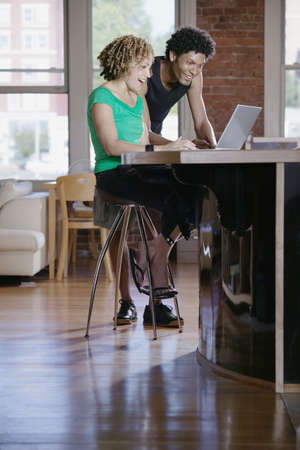 kitchen counter top: Couple working on a laptop at a kitchen counter top