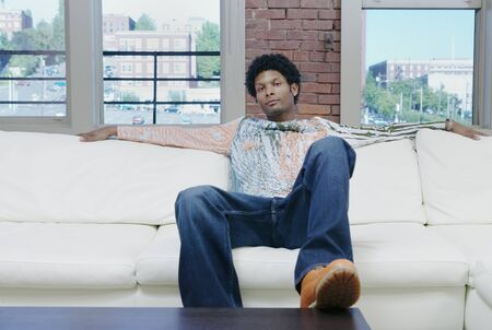 Young man sitting on a couch with his foot on the coffee table