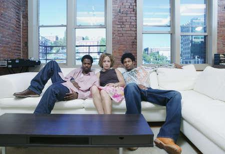 knees bent: Giovane donna e due giovani seduti su un divano