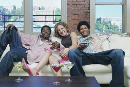three persons only: Young woman and two young men sitting on a couch