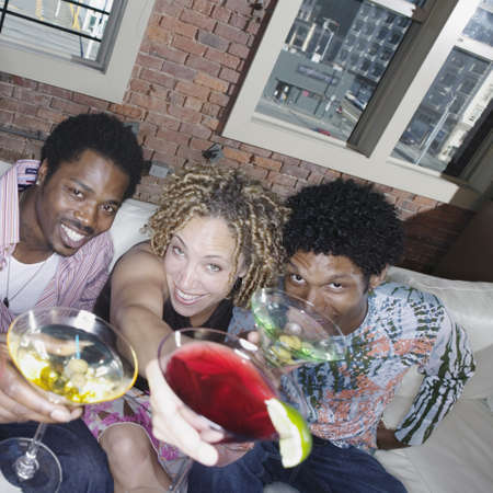 3 persons only: Young woman and two young men sitting on a couch toasting with glasses LANG_EVOIMAGES