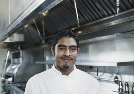 invariable: Portrait of a chef standing in a kitchen smiling