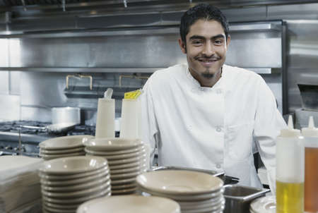 Portrait of chef standing in a kitchen smiling