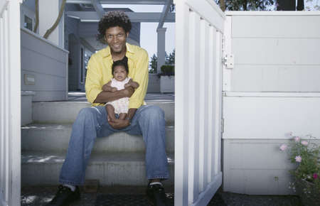 Man sitting on stairs of a house holding a baby