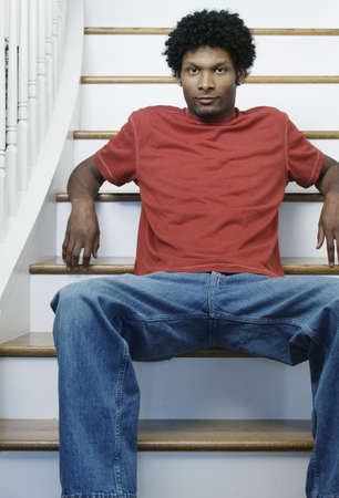 way of behaving: Portrait of a young man sitting on steps in a house