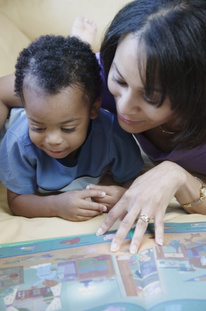 Young woman reading a book to a young boy